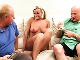 Fascinating blonde wearing blue thong confidently touching herself in front of two eager dudes on a white bed
