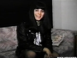 Smoking raven wearing black leather rocker jacket and fishnet stockings smiles and shows off her curves