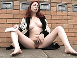 Sitting in a public place, she spreads her legs wide to expose her furry cunt
