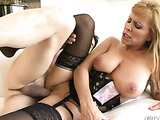 Busty blonde in black lingerie and stockings gets her shaved cunt pounded on the white couch by older guy