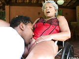 Short haired grandma in pink dress and red lingerie lets black guy lick her shaved vagina outdoors