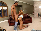 Brunette ebony in high heels and blue top giving a head to black fella on her knees before riding his cock on the couch