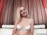 Smily blonde with big naturals posing in white bra on the white couch