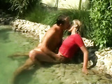 Innocent young blonde plays in the pool wearing pink top and green panty and sits on the rocks and lets her boyfriend torridly kiss her pussy