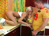 Playful young blonde wearing white top and yellow shorts loves standing in the kitchen and eating a cucumber with her guy and bending over on the kitchen counter