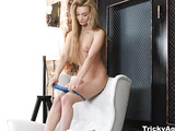 Playful blonde with smokey eyes and roange nails slowly unhooks her blue laced bra and panty by the lamp for large man holding the camera