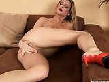 Amazing blonde in heels rubs her clit on the sofa.
