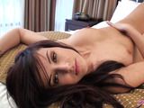 Brown-eyed brunette in a blue dress stripping on a bed