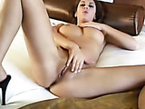 Tatted-up brunette fingering her pussy on a white bed