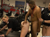 Chubby red haired police whore kneels in the crime scene and licks black guy's cock wearing red necklace while mean blonde police rubs his back