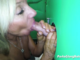 Nasty blonde milf with ocean blue eyes wearing jewelry uses both her hands on the green protable box and sucks cock through gloryhole