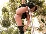 Tall latex boots brunette shows her stripper prowess outdoors on a pole