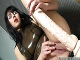 Brunette with bangs and latex get-up stroking a massive flesh-colored dildo