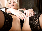 Short-haired blonde MILF in stockings masturbates on a chair