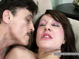 Nasty young brunette with pretty eyes wearing white tank top on her freckled shoulders and shorts kneels in the green carpetted office and sucks on old cock