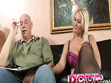 Plumpy blonde wearing black stockings and lingerie sits on the black sofa in front of large painting next to old bald guy and seduces him for sex