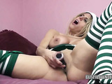 Blonde with big tits with shoulder tattoo wearing green elf costume and white and green stockings lays on the bed playing with her cunt using dildo
