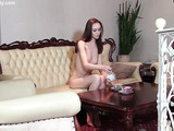 Asian teen drinks tea by the couch while spreading her shaved cunt.