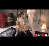 Oiled brunette blows two sausages in the dark garage