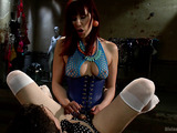 Angry red maitress in fishnet catsuit and red high heels jeering and whipping a guy before pounding him with a strap-on