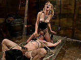 Blonde mistress in a corset ans fishnet pantyhose torturing a gagged dude bound and suspended