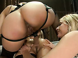Horny brunette mistress fisting asses of two cuties in stockings and pounding them with dildos and strap-on