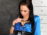 Brunette in a blue dress playing with cum from the cock in the wall