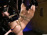 Ponytailed brunette chick all in latex mask and suit gets bound and suspended for rough sex with a bdsm masked master in latex outfit