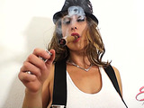 Big-titted MILF in a white vest, skirt and hat smoking a long cigar while seducing a dude
