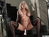 Busty blonde MILF in striped stockings jumping on a toy on the stairs