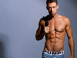 Sexy gay posing in the studio in jeans and trunks and then fondling himself