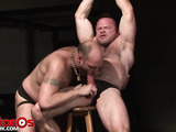 Big gay dude with his hands chained while sitting on a wooden stool gets his pierced nipples sucked by another hunk gay before they make out then he lets him pull his big dick out under his black brief and give him a blowjob before making him lick his ass