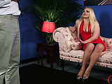 Busty blonde wearing sexy red dress and silver high heels sits on a pink couch while talking to a guy on how she likes a man in boxers.