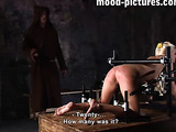 Blonde babe gets punished for refusing to electricute her friend as she was asked to take off her pink dress and was forced to bend over on a wooden box with her hands and feet bounded on black metal bars while she gets her ass whipped leaving some lash m