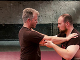 Dudes in sweatpants and shirts demonstrate grappling and takedowns for BDSM play.