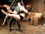 Short-haired brunette in black tights demonstrates dynamic bondage suspension.