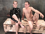 Lady in black latex demonstrates CBT or cock and ball torture at the dungeon.