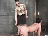 Tattooed broad in the nude takes the cane from a girl in glasses.