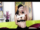 Asian hottie wearing white shirt and red and white stripes tie holds a big flesh dildo then sucks it while sitting on a green couch before she licks her armpits then displays her big juicy boobs under her black bra.