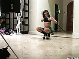 Hot cheerleader pose her sexy body in green, white and black uniform then do the split on the floor before she lifts up her shirt and expose her petite boobs.