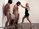 This blonde mistress in red spiked high heels gives painful pleasure to two masked slaves