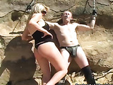 Blonde female tortures helpless man chaining him to a rock