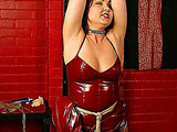 Attractive red-haired lady in latex costume got tied up