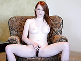 Stunning redhead takes off her pink and white skirt then bends over and shows her sexy butt before she strips off her white blouse and black panty and stabs her twat with a black dildo in different positions on a brown couch on wearing her black high heel
