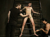 Tied up gay dude gets his long dong stroked by two men