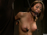 Brunette vixen gets orgasm while getting her tits teased with threads and pins in bondage device