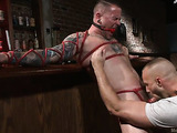 Tied up man gets his dick sucked in the bar so well