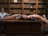 Two tied up gay hunks get teased in the library