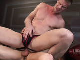 Homo in a red and black jockstrap rides a buddy in bed.