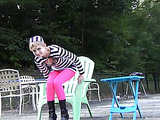 Skinny hottie with short blonde hair pose outdoor then takes off her black and white striped shirt and expose her small tits while she rubs her twat wearing her pink stockings and black boots on a green chair.